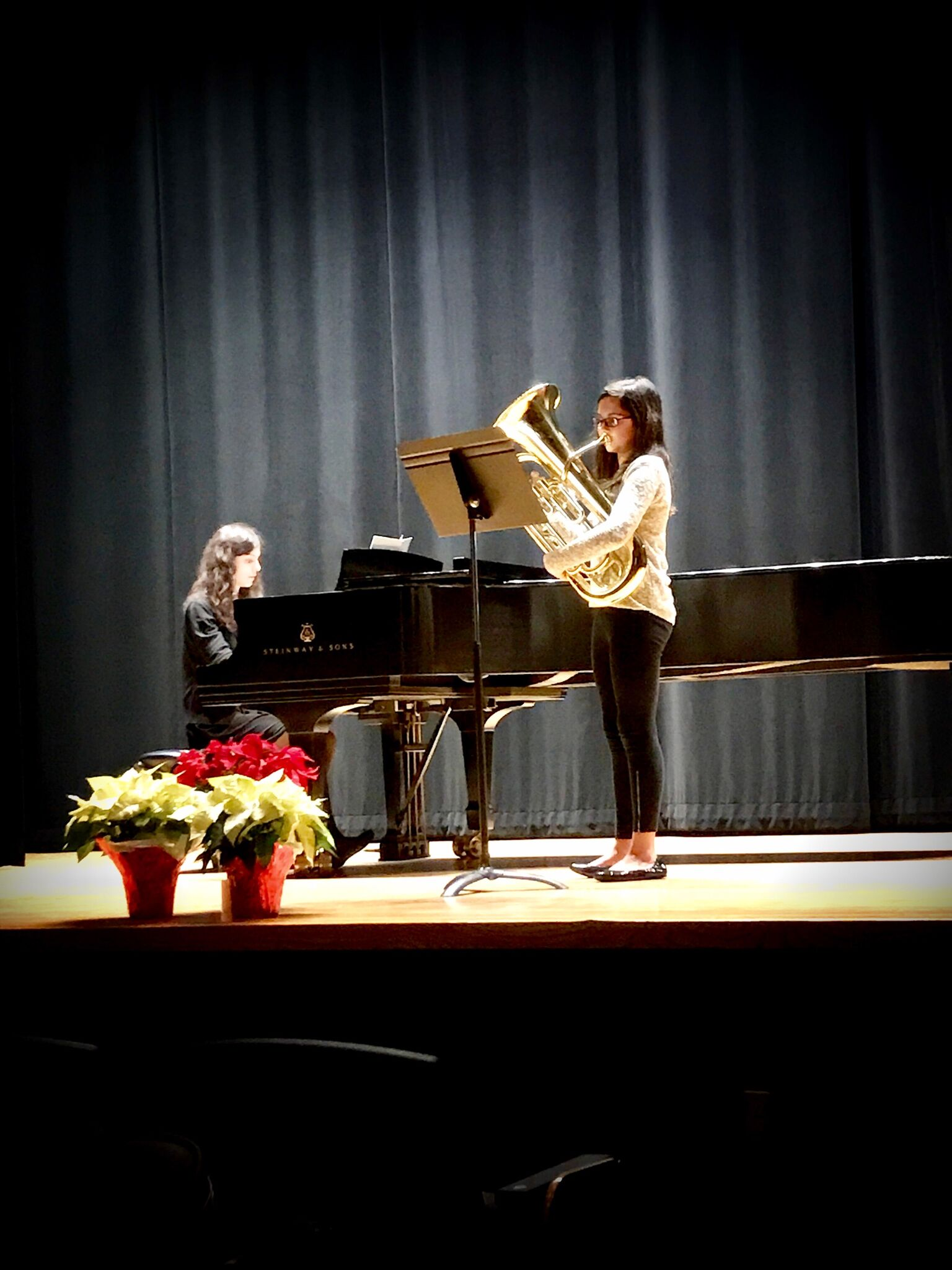 a young student performs on tuba while accompanied on piano