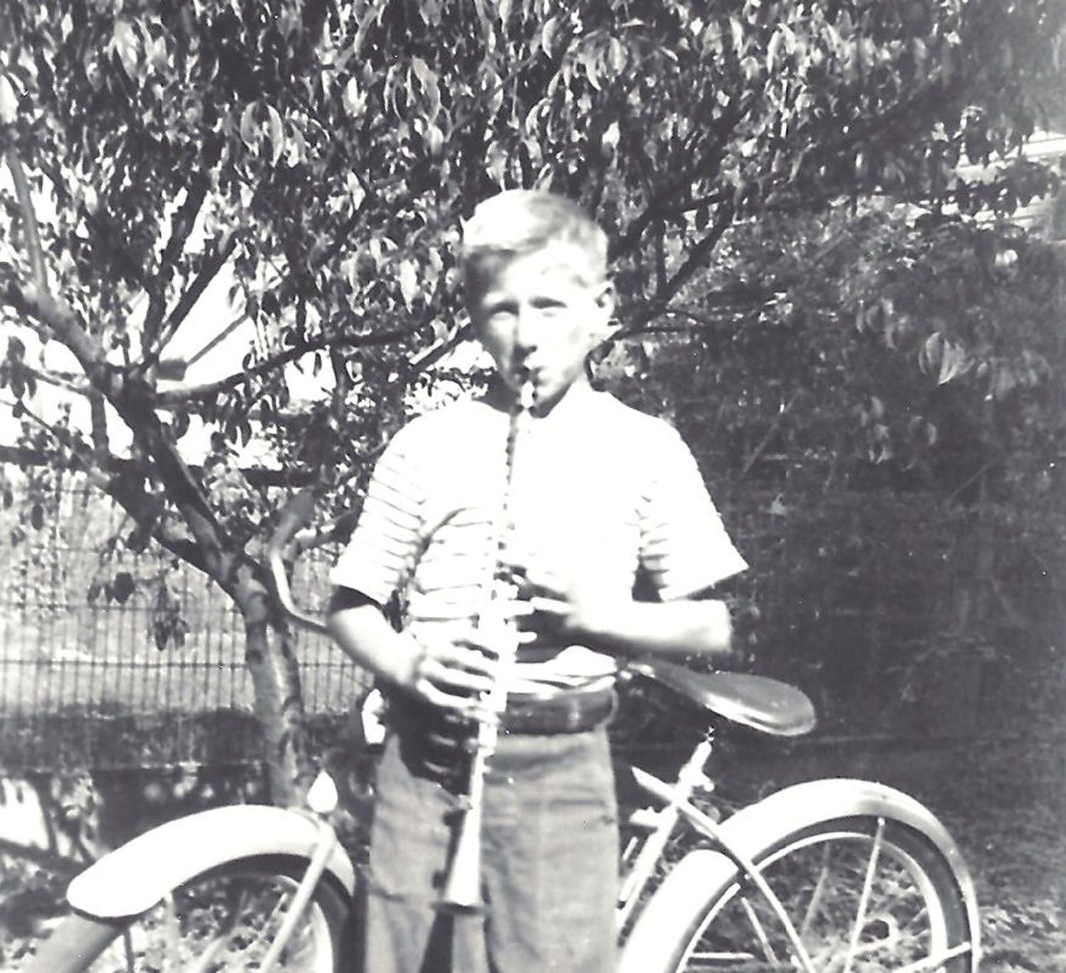 old photo of Don Gephardt as a boy playing clarinet in front of his bicycle