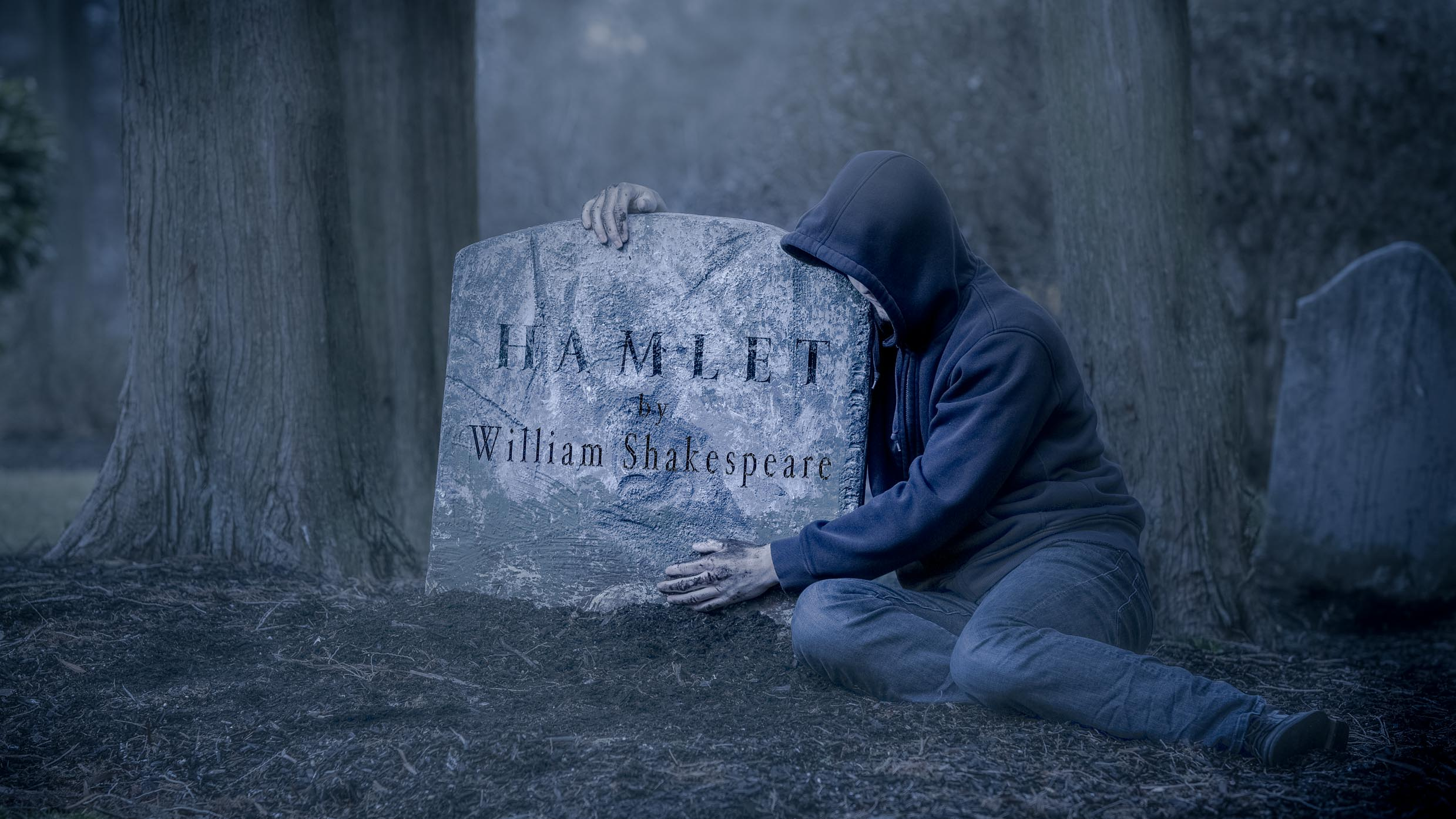 "A person their arms around a tombstone that reads ""Hamlet by William Shakespeare"""