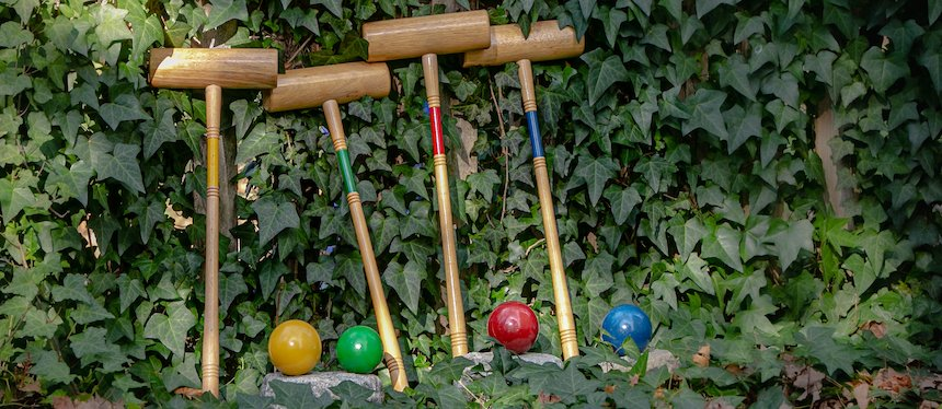 four croquet mallets leaning against a wall of ivy with four coordinating colored croquet balls