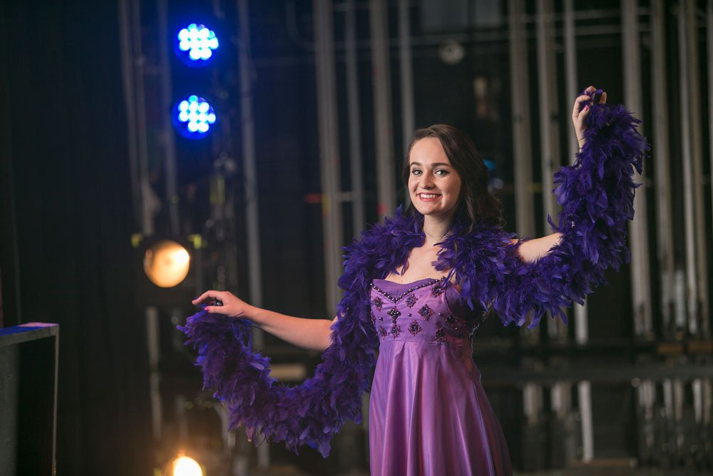 wearing a purple dress and a feather boa, a female student smiles broadly with her left arm outstretched